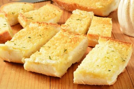 garlic: Fresh baked sliced garlic bread on a rustic wooden cutting board