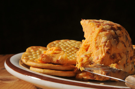 A cheddar cheese ball with nuts and whole wheat crackers