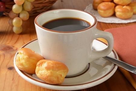 Una taza de café negro con mini bollos de crema Foto de archivo - 31217654
