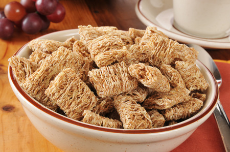 A bowl of shredded organic wheat biscuits with a cup of coffee Stock Photo