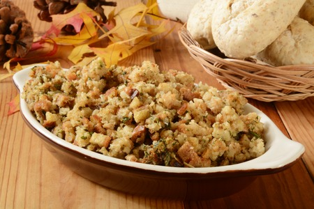A bowl of turkey stuffing with dinner rolls on a holiday table