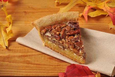 A slice of pecan pie with autumn leaves on a rustic wooden counter