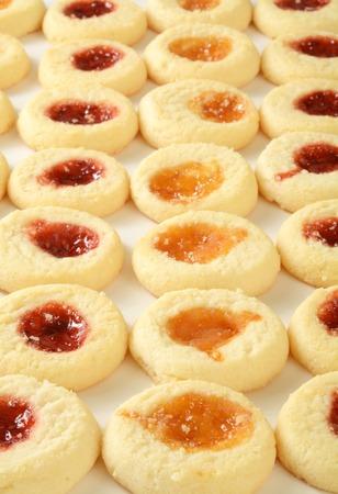 Rijen shortbread cookies gevuld met aardbei en perzik jam Stockfoto