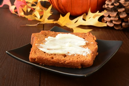 buttered: Buttered slices of pumpkin bread on a holiday decorated table