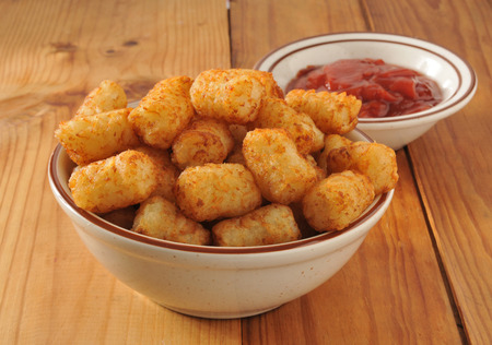 tots: A bowl of deep fried potato puffs with catsup Stock Photo