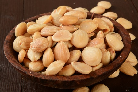 nuts: A small wooden bowl of marcona almonds with salt and rosemary Stock Photo