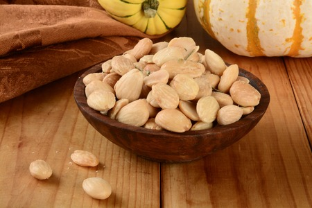A wooden bowl of Marcona almonds on  a table with squash gourds Stok Fotoğraf - 32485457