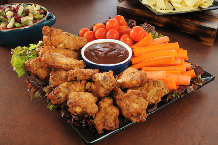 A holiday snack platter with chicken wings, carrot sticks, cherry tomatoes, salads, and chips