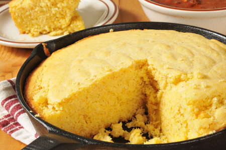 skillet: Corn bread in a cast iron skillet with a bowl of chili in the background
