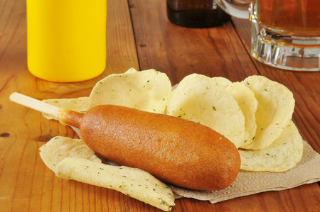 A corn dog with sour cream and onion potato chips and a mug of beer photo