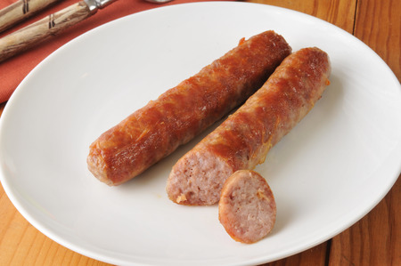 Grilled beer sausage on a plate with a slice out of it Stock Photo