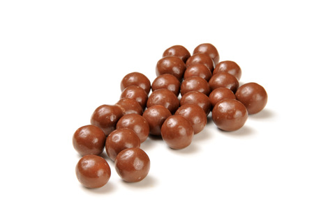 malted: An arrangement of chocolate covered malted milk balls on a white background