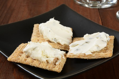 Wheat crackers with cream cheese and chives served as an appetizer