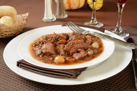 braised mushrooms: A plate of Boeuf Bourguignon or Beef Burgundy with dinner rolls
