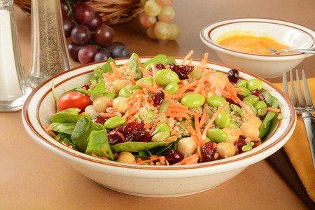 A healthy salad with chickpeas, edamame, pumpkin seeds, quinoa, spinach, and miso dressing Stock Photo