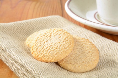 Krokante citroen snap cookies op een servet met een kopje koffie Stockfoto