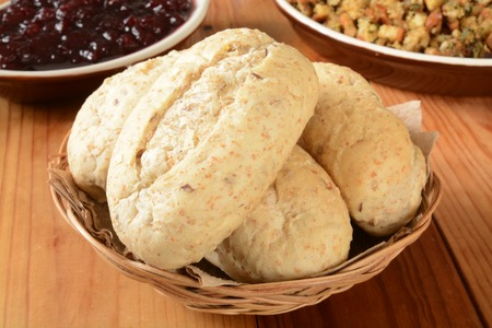 A basket of multi grain dinner rolls with stuffing and cranberry sauce