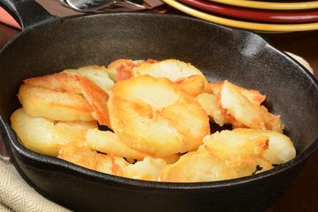 백그라운드에서 접시를 제공하는 숙련 된 주철로 된 홈 튀긴 감자