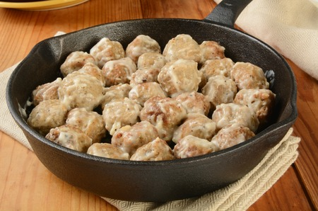 A cast iron skillet of Swedish meatballs in cream sauce