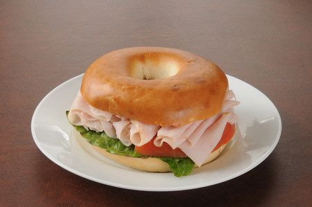Ham sandwich on a bagel with lettuce and tomato