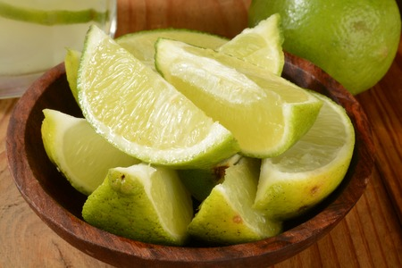 Fresh lime wedges in a wooden bowl with a gimlet in the background