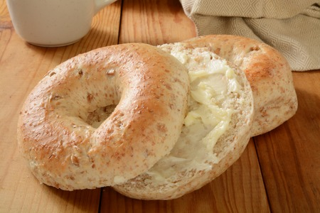 multi grain: A sliced multi grain bagel with butter and a cup of coffee Stock Photo