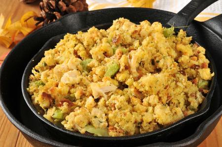 cornbread: cornbread stuffing with chunks of turkey in cast iron skillets