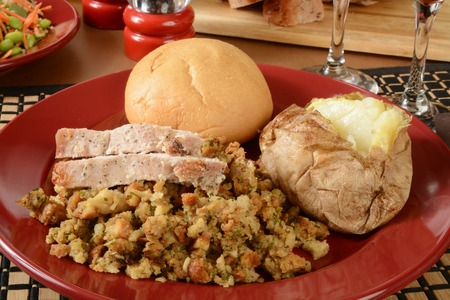 stuffing: Thick slices of turkey on stuffing with a baked potato