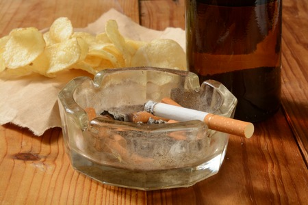 junk: A cigarette buring in a dirty ash tray with potato chips and beer