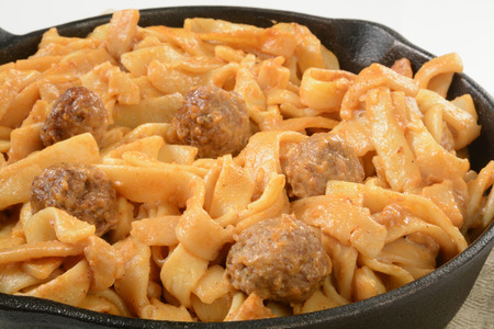 Closeup of swedish meatballs with gravy and noodles in a cast iron skillet