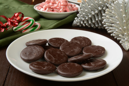 A plate of chocolate mint cream cookies with candy canes and peppermints for Christmas