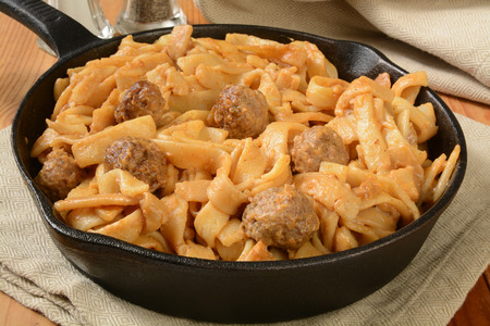 Swedish meatballs with gravy and pasta in a cast iron skillet Stock fotó