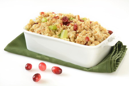 A baking dish of stuffing with cranberries and celery on a white background