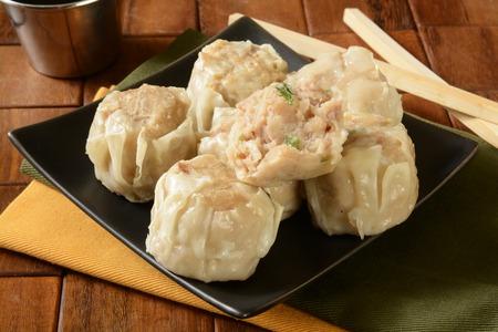 chop sticks: A dish of pork shu mai with chop sticks Stock Photo