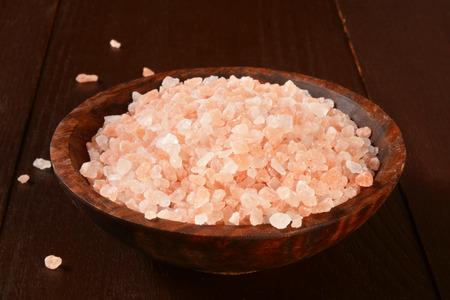A wooden bowl of course ground Himalayan salt