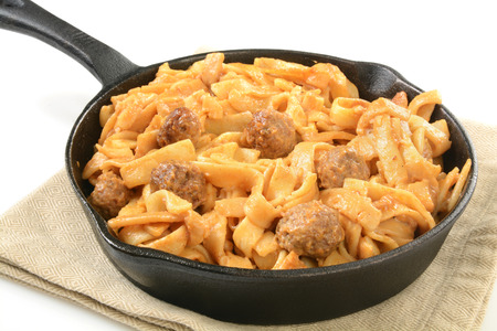 Swedish meatballs with noodles and gravy in a cast iron skillet