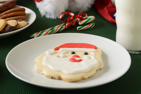 clause: A sugar cookie shaped like Santa Clause with milk