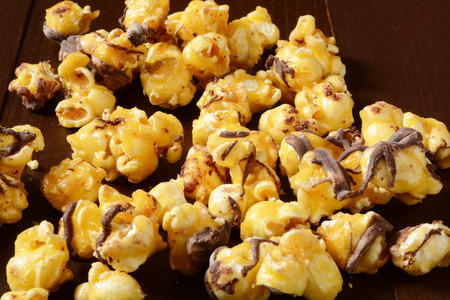 Gourmet popcorn with carmel and chocolate on a rustic wooden table