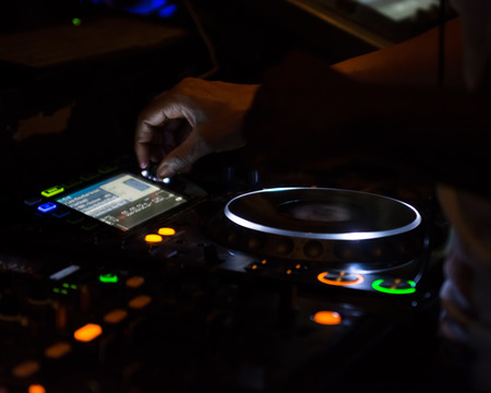 control panel lights: Close up of a DJ adjusting the controls on his mixing station Stock Photo