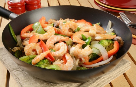Shrimp stir fry in a wok with serving plates in the background