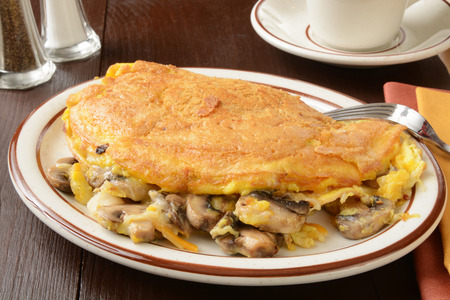 A mushroom and swiss cheese omelette with a cup of coffee Banco de Imagens