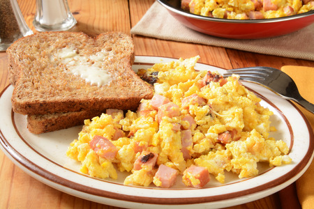 wheat toast: Scrambled eggs with diced ham and cheese and hot buttered sprouted whole wheat toast Stock Photo