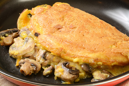 Closeup of a mushroon and cheese omelet in a frying pan