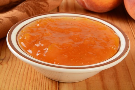 A small bowl of peach jam on a wooden table with fresh peaches i the background