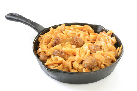 Swedish meatballs and gravy on pasta in a cast iron skillet