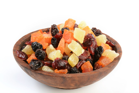 A wooden bowl of dried fruit on a white background