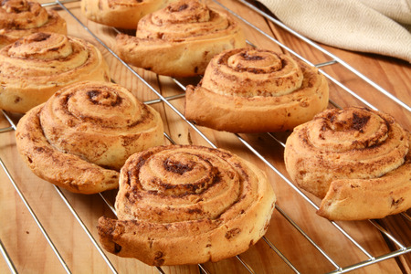 Fresh baked cinnamon rolls on a cooling rack Stock Photo