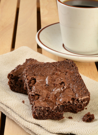 home cooked: Fresh baked home made brownies on a napkin with a cup of coffee
