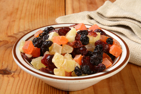 A small bowl of dried fruit on a rustic wooden counter