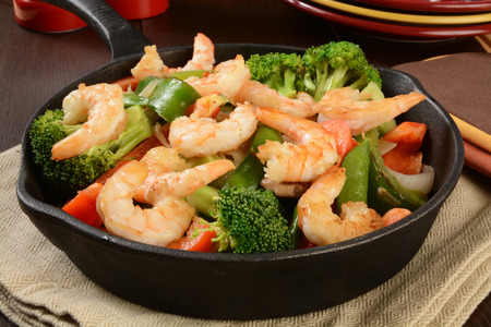 Shrimp stir fry in a cast iron skillet Stock Photo